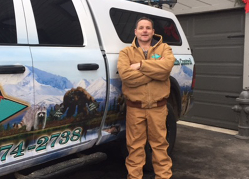 Man standing beside the wildlife removal truck