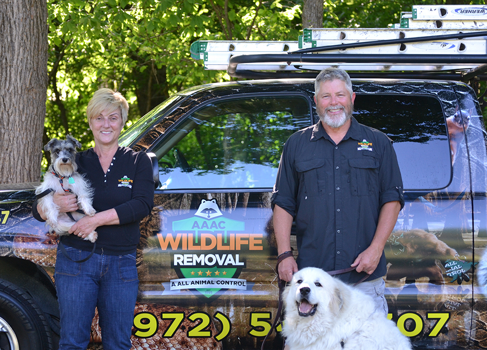 Wildlife Removal Owners beside a truck