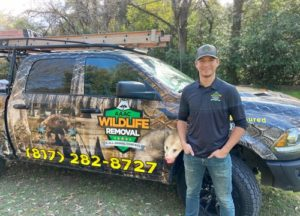 Christian standing beside the wildlife removal truck