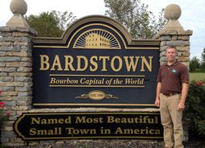 Man posing beside Bardstown sign