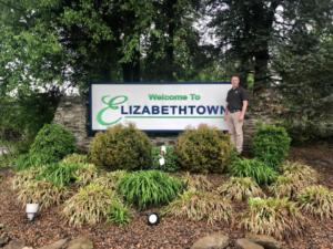 Owner, Vince, posing next to Elizabethtown sign
