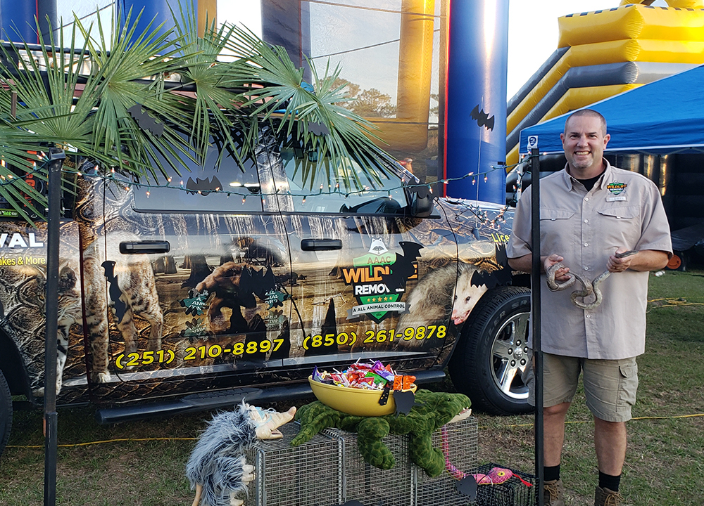 AAAC Wildlife Removal specialist holding a snake at a fair.