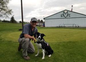 Man & dog posing at golf course