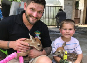 Owner Jeremiah Crampton and a little boy smiling and each holding a very young bambi.