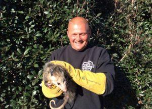 Man holding a opossum