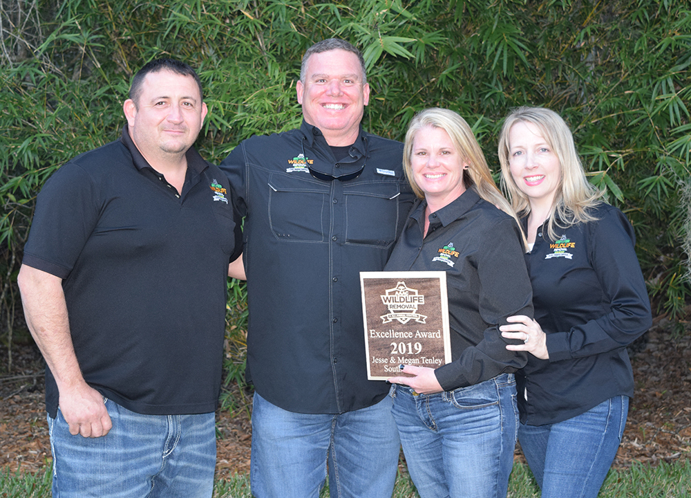 Wildlife Removal owners posing for a group photo holding a certificate of excellence award